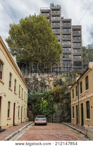 Sydney Australia - March 22 2017: The cul-de-sac short Adherden street end against a cliff. Yellow painted houses. On top of cliff modern high rise and big green tree. Can in street.