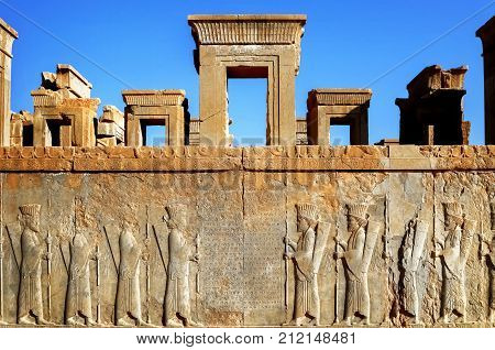 Persepolis is the capital of the ancient Achaemenid kingdom. sight of Iran. Ancient Persia. Bas-relief carved on the walls of old buildings against the blue sky.