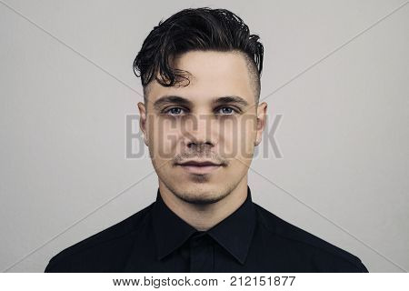 Portrait of man in formal clothing (shirt) and perfect clean skin on grey background with studion light Illuminated portrait of handsome male model with modern hairstyle. Fashion formal portrait.