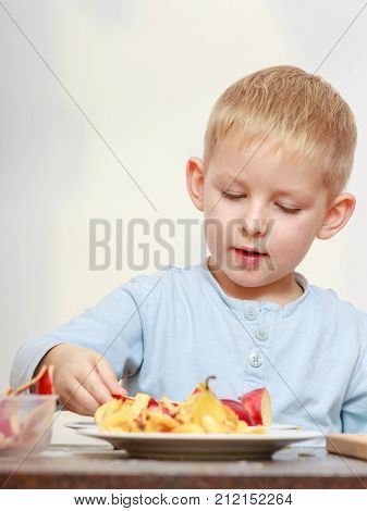 Little Boy Peeling Apples With Knife And Eating
