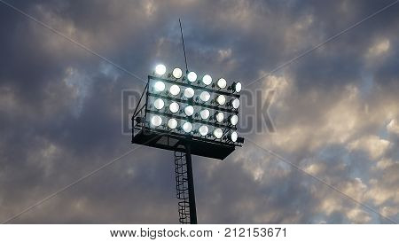 Stadium flood lights on a sports field at night with copy space.