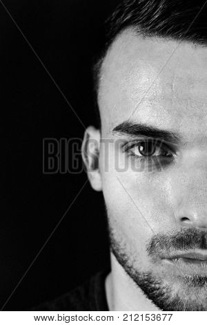 Portrait of beautiful  young man with green eyes on dark black and red  background. Half face portrait of man with beard and sharp lines of face. Attractive guy half face close up photo.
