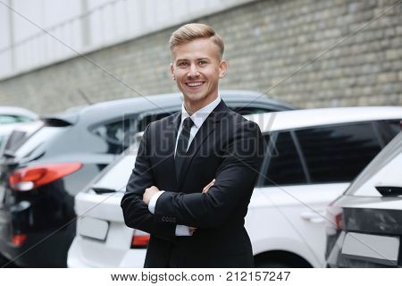 Young car salesman in formal suit near parked automobiles outdoors