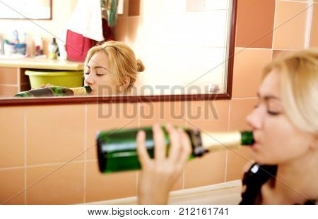 Teen woman drinking alcohol in bathtube.