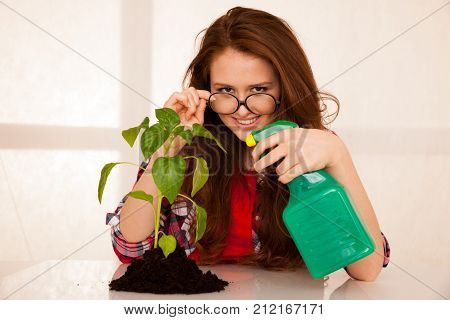 attractive young woman botanist spraying a seedling