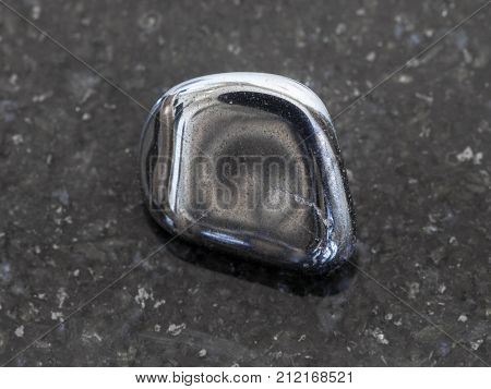 Tumbled Hematite Gem On Dark Granite Background