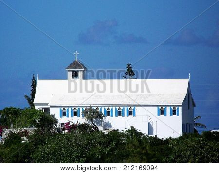 island church building sitting on hill with green vegetation with steeple and cross