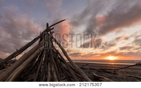 Dirft wood stack up at a beach with a sunset sky behind it.