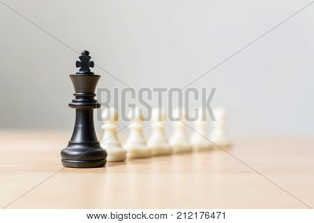 Black chess figure leading white chess on wood table Success of business leader concept