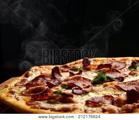 Hot big pepperoni pizza tasty pizza composition with melting cheese bacon tomatoes ham paprika steam smoke on black background