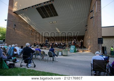 JOLIET, ILLINOIS / UNITED STATES - JUNE 1, 2017: Dr. Lawrence Sisk conducts the Metropolitan Youth Symphony Orchestra (MYSO), in a free public concert at the outdoor theater in the Billie Limacher Bicentennial Park.