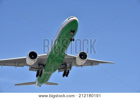 Very close up of the underside of a jumbo jet landing