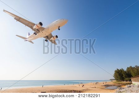 Airplane is landing at Phuket airport over the Mai Khao beach Thailand