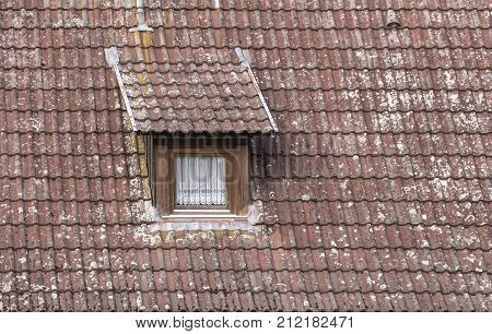 detail of a old roof with dormer and window