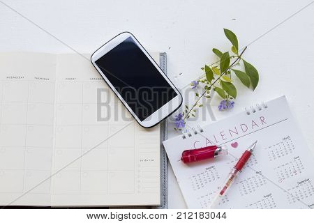 notebook with calendar yearly planner and mobile for financial on white
