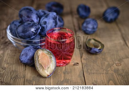 Traditional homemade plum liqueur and berries plums on a rustic table. A homemade alcoholic drink made from plums.
