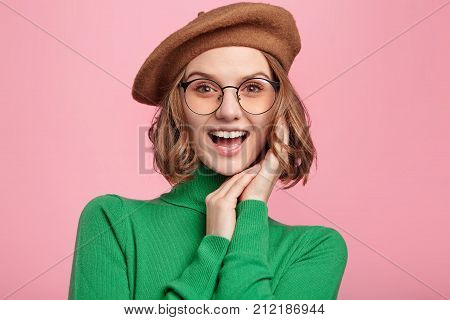 Gratified pleasant looking woman in beret and spectacles rejoices hearing good news glad to be promoted. Female recieves proposal from boyfriend being overjoyed smiles happily. Happiness concept poster