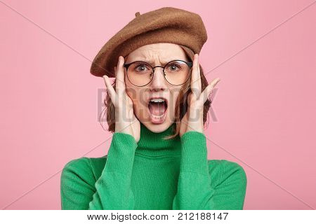 Portrait Of Indignant Shocked Pretty Female Wears Beret, Green Turtleneck Sweater And Glasses, Keeps