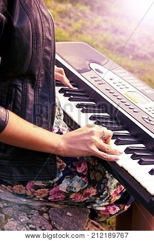 Attractive girl playing a synthesizer on nature. A woman is 25-30 years old. An electric piano stands in nature