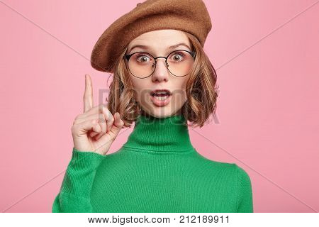 Adorable Beautiful Young Woman Gets Good Idea In Mind How Improve Project, Raises Fore Finger, Wants