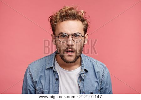 Curious Scrupulous Male Model With Trendy Hairrdo And Beard Looks Attentively At One Point, Sees Som