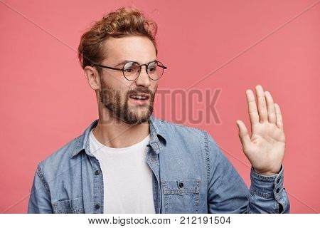 Sideways Portrait Of Fashionable Young Male Notices Someone, Greets Reluctantly, Waves With Palm Unw