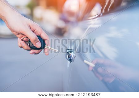 Business man holding car keys for opening car door. Hand of businessman locked or unlocked car by car key.