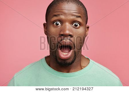 Indoor Picture Of Scared Bugged Eyed African American Male Looks With Bated Breath, Horrified To Hea