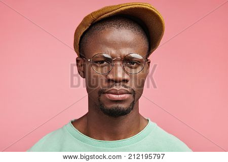 Stern Serious Dark Skinned Male Looks Through Spectacles, Frowns Face In Dissatisfaction, Displeased
