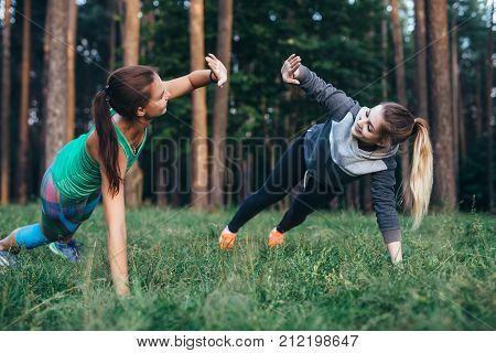Two female buddies doing partner side plank giving high five while training in the forest.