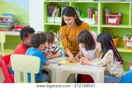 Asian female teacher teaching mixed race kids reading book in classroomKindergarten pre school concept