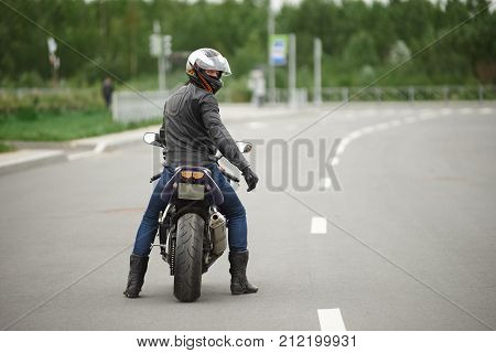 Sports extreme speed adrenaline and determination concept. Rear view of stylish biker in leather clothes and safety helmet riding his motorcycle along empty high way turning face to camera