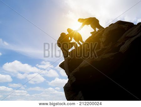 Asia couple hiking help each other silhouette in mountains with sunlight. couple hiking help each other silhouette in mountains with sunlight