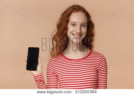 Closeup Of Young Smiling Pretty Curly Redhead Girl In Striped T-shirt, Holding And Showing Blank Sma