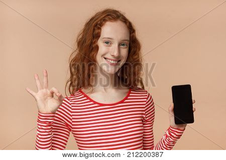 Indoor Portrait Of Attractive Pretty Curly Redhead Girl, Holding Blank Smartphone, Smiling At Camera