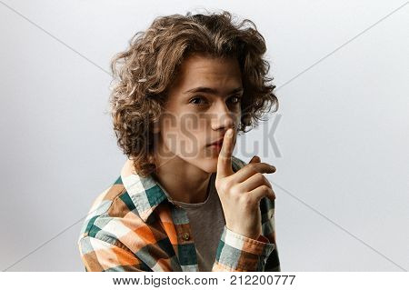 Picture of attractive young man in trendy clothes posing in studio with finger on his lips staring at camera with mysterious look saying Shh keeping some confidential information a secret