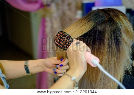 Hair dresser showing blonde female hair with bad hair extension.