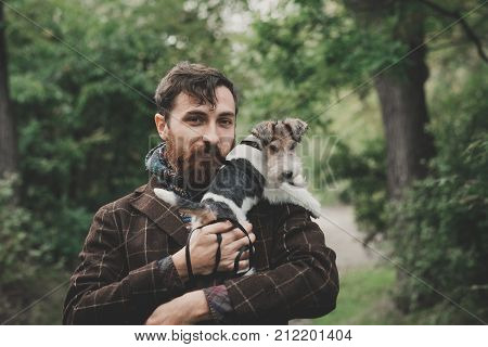Dog and his owner - Cool dog fox terrier and young man having fun in a park - Concepts of friendship,pets,togetherness
