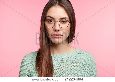 Portrait Of Attractive Young Female With Asian Appearance Wears Spectacles, Loos Seriously At Camera