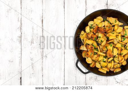 Fried potatoes in a cast iron pan on light wooden background top view