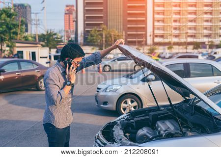 Young asian handsome man standing by the Broken Down car and calling for help with smart phone