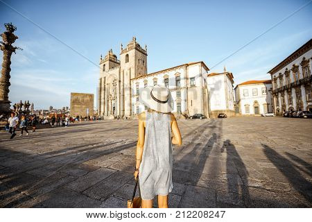 Young woman tourist in sunhat standing back in front of the main cathedral in Porto city during the sunset in Portugal
