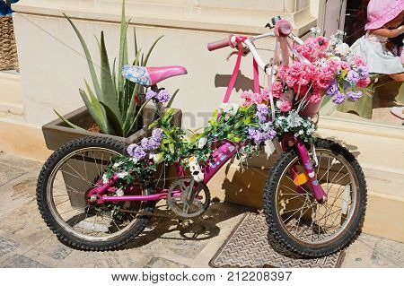 RETHYMNO, CRETE - SEPTEMBER 15, 2016 - Girls pink bike decorated with flowers along a shopping street in the old town Rethymno Crete Greece Europe, September 15, 2016.