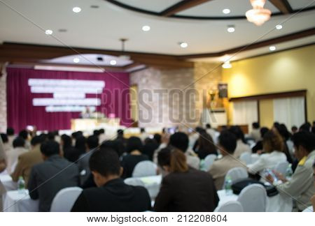 Audience listening speaker speech in conference hall or seminar room with blur light people background. Seminar is form of academic instruction offered by commercial or professional organization.