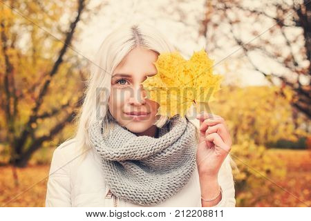 Autumn Woman with Maple Leaf in Fall Park