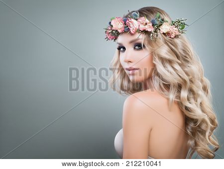 Beautiful Lady Fashion Model with Roses Flowers and Green Leaves in her Hair. Cute Woman with Blonde Curly Hairstyle and Healthy Skin Skincare and Haircare Concept