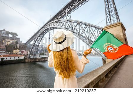 Young woman traveler in sunhat standing back with portuguese flag with the famous iron bridge on the background in Porto city