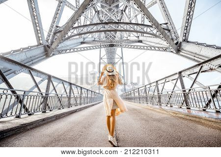 Morning view on the famous Luis bridge with woman walking during the foggy and windy weather in Porto city, Portugal