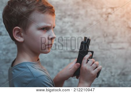 Boy with gun in hand against a brick wall, reloading the gun, dramatic portrait