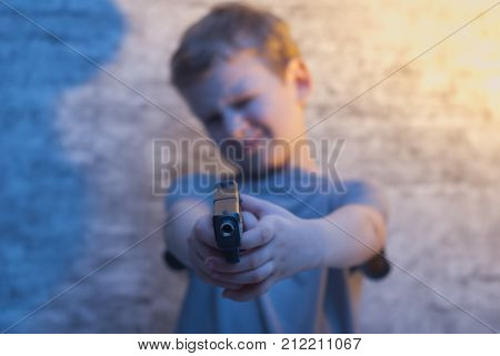 the boy with the gun pointing, selective focus on the barrel of the gun, the concept of bad parenting